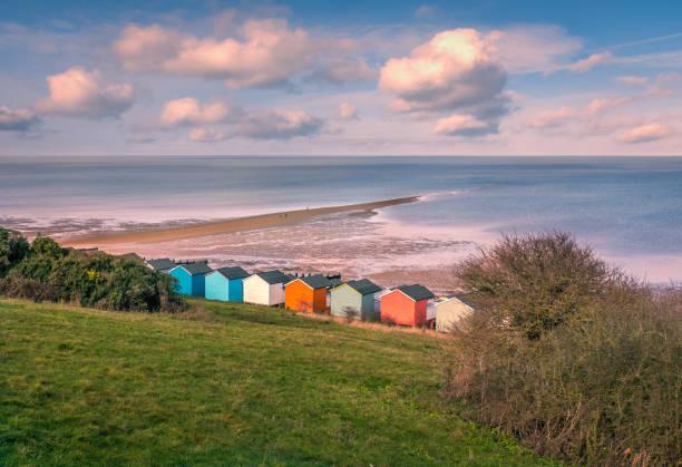 Beeindruckende Winter Wolken in einem kühlen blauen Himmel über den Strandhütten und natürlichen Spieß von Land, das Meer am Strand in Tankerton, Whitstable, Kent, UK streckt. Drei Personen sind auf die natürliche und lokal benannte Straße flanieren – Foto