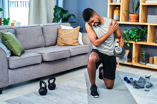 Shot of a young man suffering from shoulder pain while exercising at home