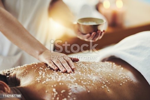 Closeup shot of a woman getting an exfoliating massage at a spa