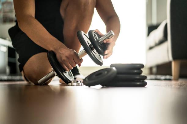 verbesserung und immer stärker in fitness, bewegung und muskel-trainingskonzept. mann, verstellbare hantel im hause fitness-studio mehr gewicht hinzufügen. - verstellbar stock-fotos und bilder