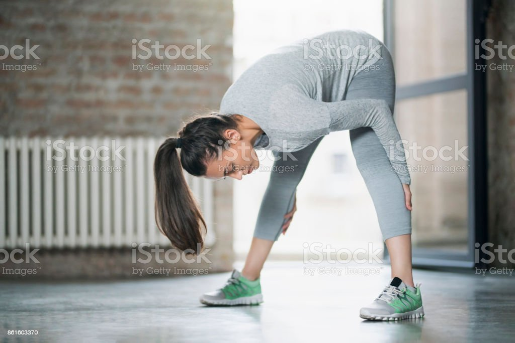 Beautiful young woman stretching her muscles after daily workout.