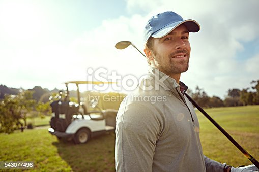 Portrait of a young man holding a golf club while enjoying a day on the golf course