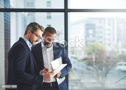 Shot of two businessmen using a digital tablet together at work