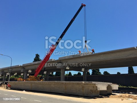 Buenos Aires, Argentina - December 15, 2018: Workers on top of elevated structures building an elevated railroad track for the train to go through it. The government is investing a lot of money in infrastructure