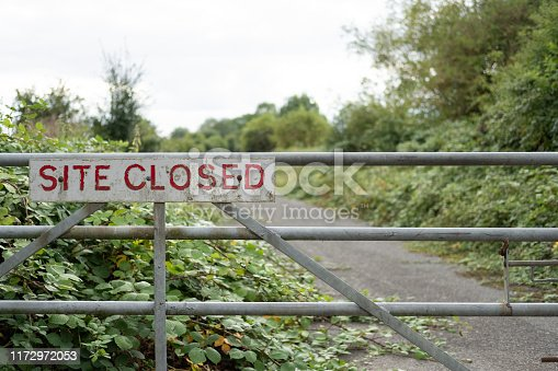 istock Improvised Site Closed sign seen on the entrance to a once busy factory. 1172972053