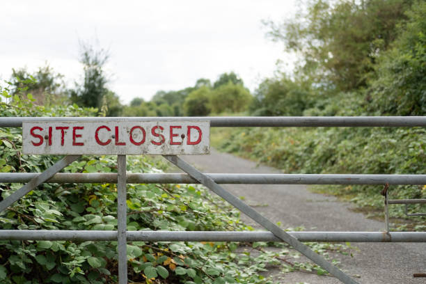 Improvised Site Closed sign seen on the entrance to a once busy factory. Vegetation is starting to take hold of the access road beyond the gate. entrance sign stock pictures, royalty-free photos & images