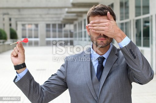 istock Impulsive businessman playing darts in office space 888846572
