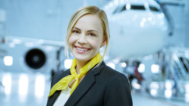 In a Aircraft Maintenance Hangar Young Beautiful Blonde Stewardess/ Flight Attendant Smiles Charmingly on Camera. In the Background Brand New Airplane is Visible. In a Aircraft Maintenance Hangar Young Beautiful Blonde Stewardess/ Flight Attendant Smiles Charmingly on Camera. In the Background Brand New Airplane is Visible. cabin crew stock pictures, royalty-free photos & images