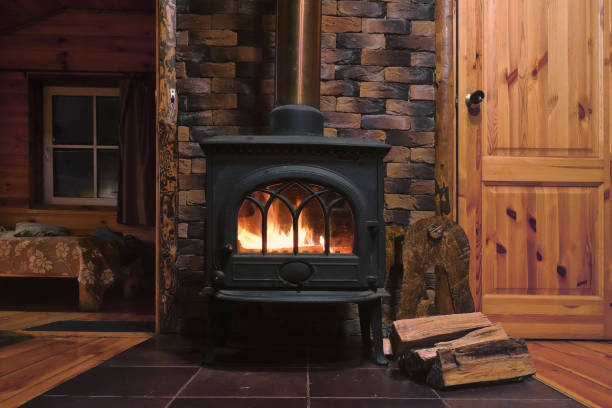 In a cast-iron furnace, a fire burns. There is wood near the stove. Fragment of the interior of a country house. The iron furnace is heated. There is wood near the stove. It's dark outside the window. stove stock pictures, royalty-free photos & images