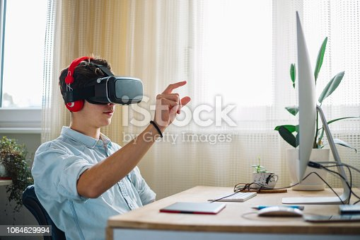 682285886 istock photo In a Computer Science Class Boy Wearing Virtual Reality Headset Works on a Programing Project 1064629994