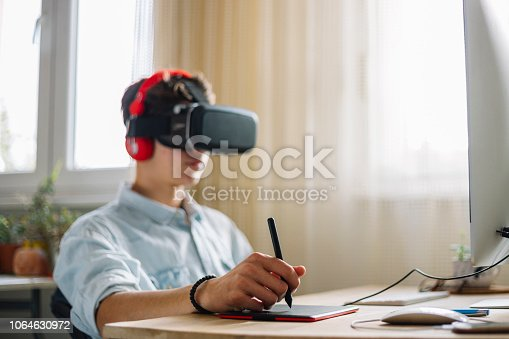 682285886 istock photo In a Computer Science Class Boy Wearing Virtual Reality Headset Works on a Programing Project 1064630972