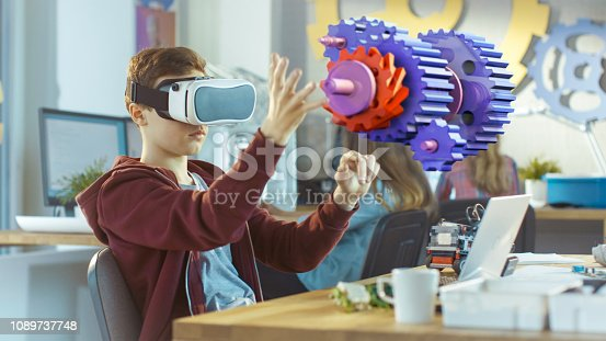 682285886 istock photo In a Computer Science Class Boy Wearing Virtual Reality Headset Works in Interactive 3D Environment. Mechanical Modeling Project of Connecting Gears with Augmented Reality Software. 1089737748