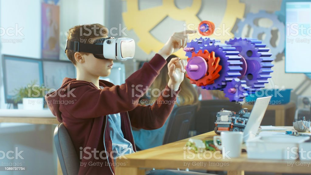 In a Computer Science Class Boy Wearing Virtual Reality Headset Works in Interactive 3D Environment. Mechanical Modeling Project of Connecting Gears with Augmented Reality Software. stock photo