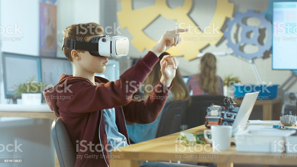 In a Computer Science Class Boy Wearing Virtual Reality Headset Works on a Programing Project. stock photo