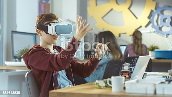 682285886 istock photo In a Computer Science Class Boy Wearing Virtual Reality Headset Works on a Programing Project. 831613836