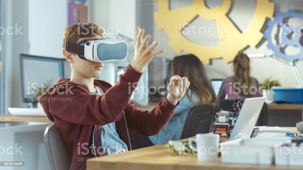 Em um computador ciência classe menino usando realidade Virtual fone funciona em um projeto de programação. - foto de acervo