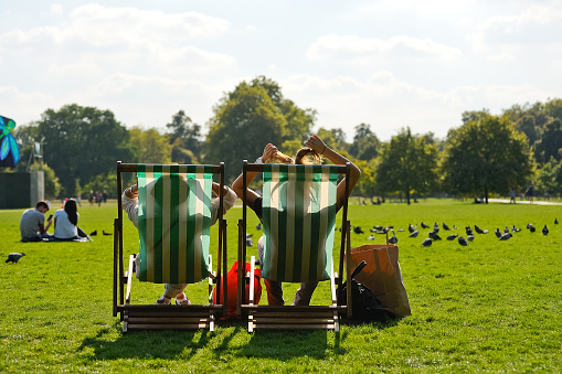 In a deck chair relaxing in Hyde Park