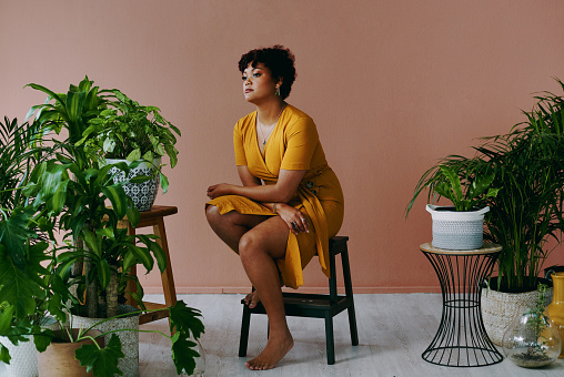 Shot of a young woman sitting on a stool with plants around her at home