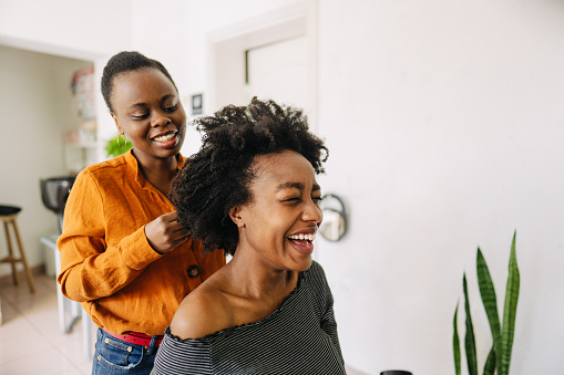 Photo of a young African American hairdresser, blow drying hair of her customer in a hair salon.