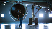 istock In a Hangar Aircraft Maintenance Engineer/ Technician/ Mechanic Inspects with a Flashlight Airplane's Jet Engine. 1022905204