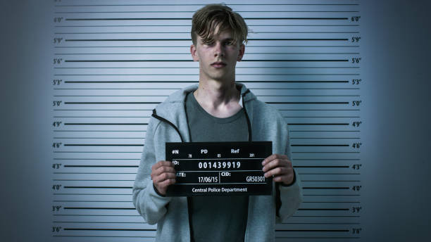 In a Police Station Arrested Drug Addict Teenage Posing for a Front View Mugshot. He is Heavily Bruised. Height Chart in the Background. In a Police Station Arrested Drug Addict Teenage Posing for a Front View Mugshot. He is Heavily Bruised. Height Chart in the Background. criminal stock pictures, royalty-free photos & images