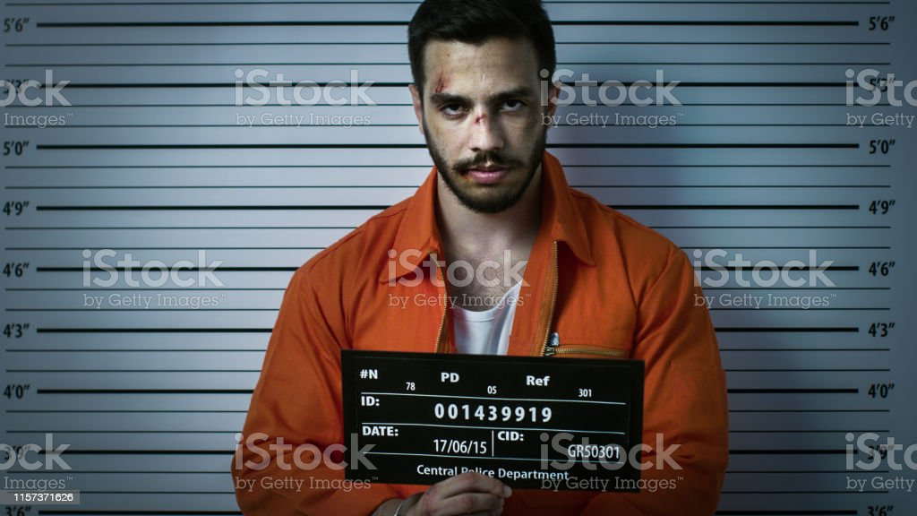 In a Police Station Arrested Man Getting Front-View Mug Shot. He\'s...