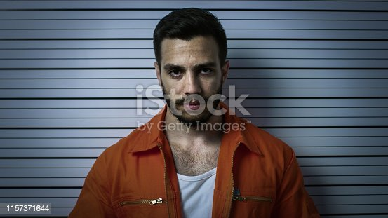 In a Police Station Arrested Man Posing for Mugshot. He's in a Prisoner Orange Jumpsuit. Height Chart in the Background.