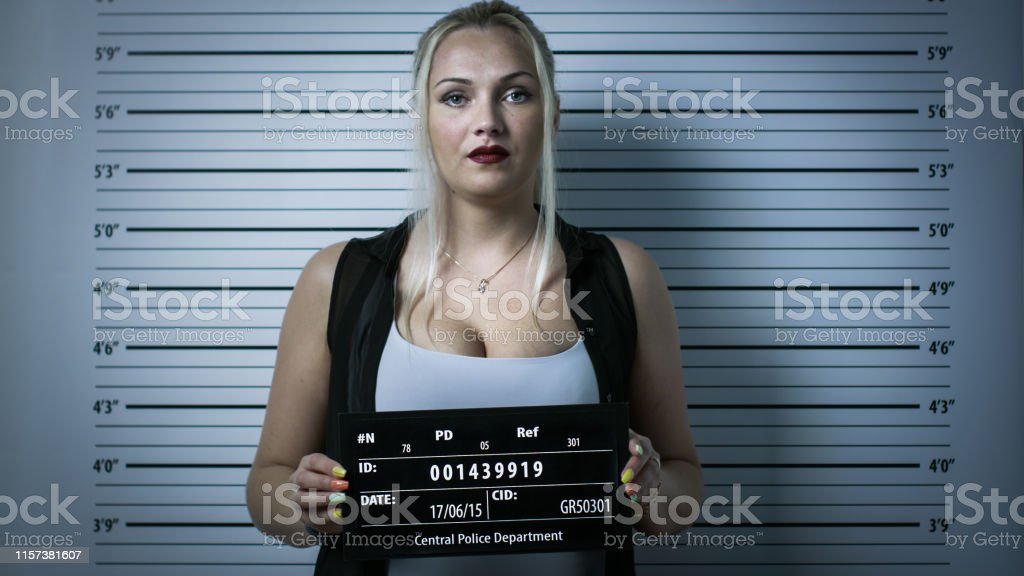 In a Police Station Arrested Woman Gets Front-View Mug Shot. She...