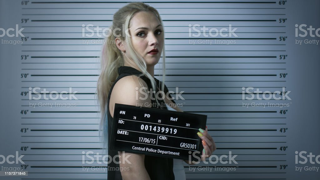In a Police Station Arrested Woman Gets Side-View Mug Shot. She Wears...