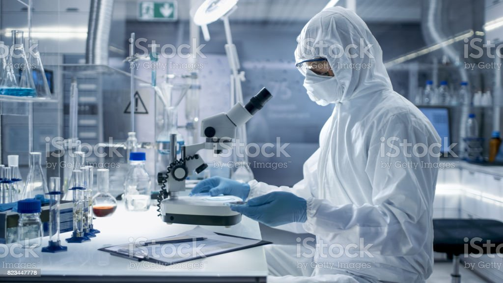 In a Secure High Level Laboratory Scientists in a Coverall Conducting a Research. Biologist Adjusts Samples in a Petri Dish with Pincers and Examines Them Under Microscope. stock photo
