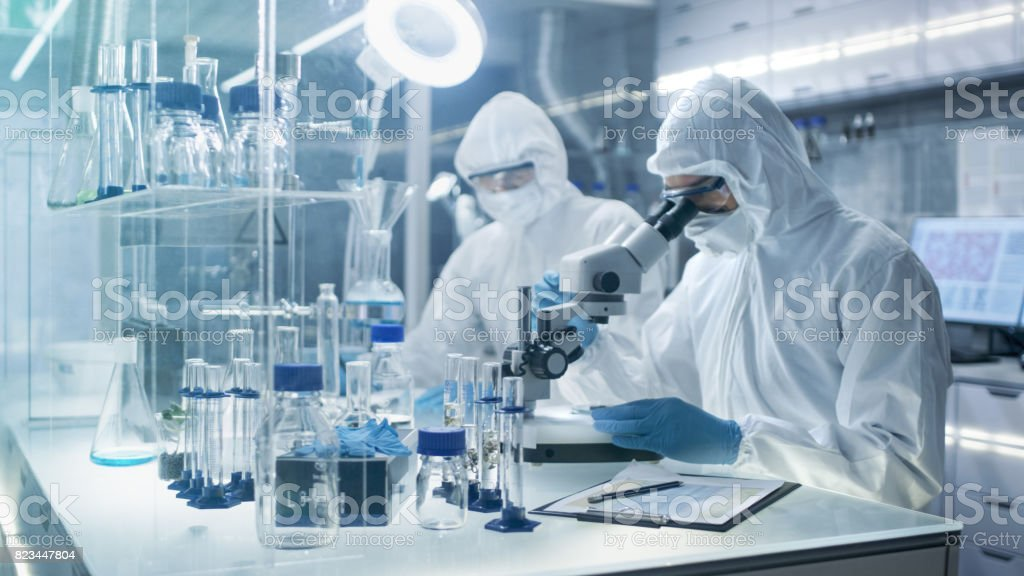 In a Secure High Level Laboratory Scientists in a Coverall Conducting a Research. Chemist Adjusts Samples in a  Petri Dish with Pincers and then Examines Them Under Microscope and His Colleague Writes Down Results. stock photo