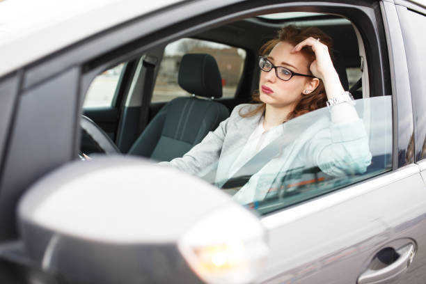In a traffic jam Attractive red hair businesswoman stuck in a traffic jam.Running late to work. traffic jam stock pictures, royalty-free photos & images