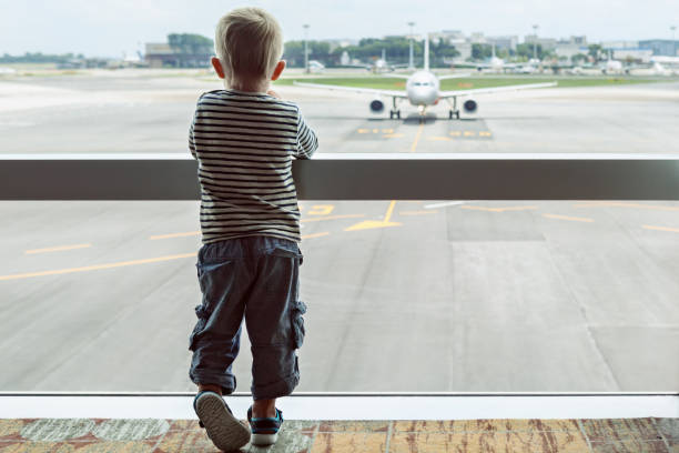 In airport hall child looks at the plane through window stock photo