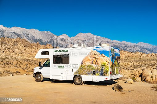 RV is parked in the Alabama Hills with the Sierra Nevada Mountain Range in the background in Lone Pine, California, USA on a sunny day.