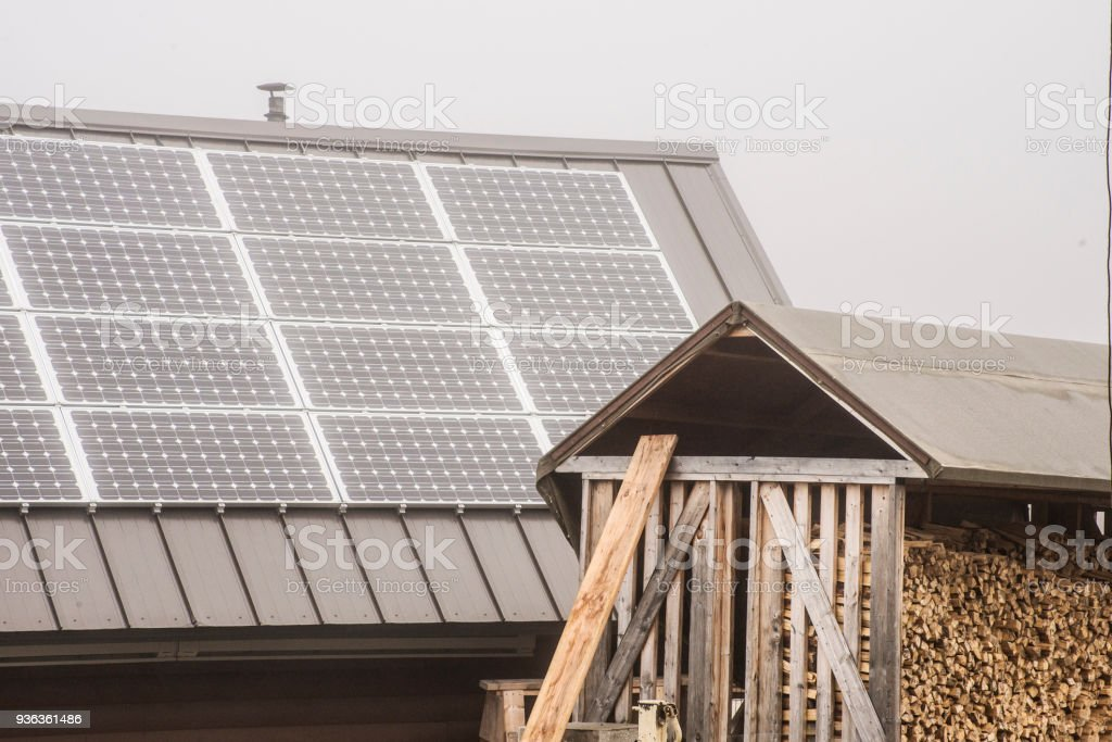 In Alaska, solar panels, and a shed full of chopped wood, getting ready for winter season. stock photo
