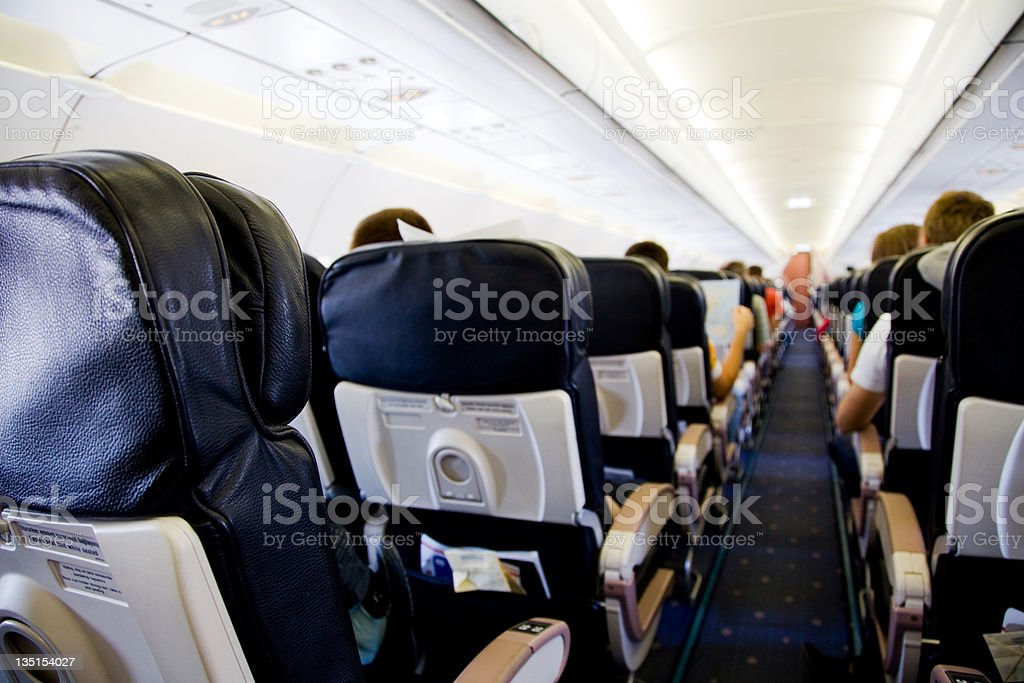 In an airplane cabin douring flight...passengers on seats royalty-free stock photo