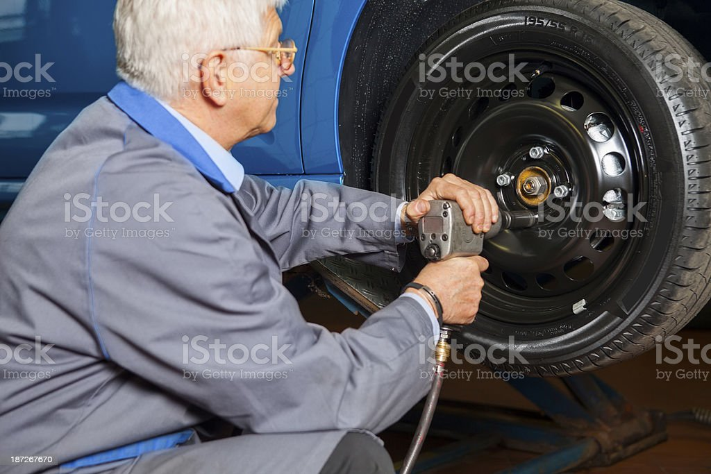 In auto repair shop Car mechanic is changing tire stock photo