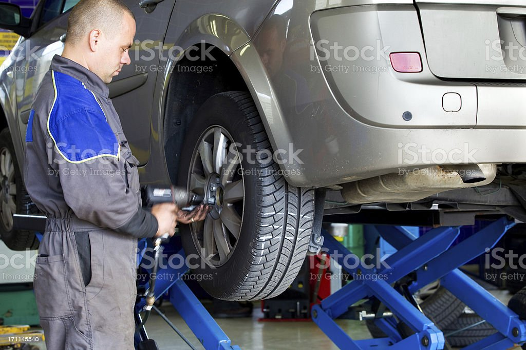 In auto repair shop....Auto mechanic is changin tire stock photo