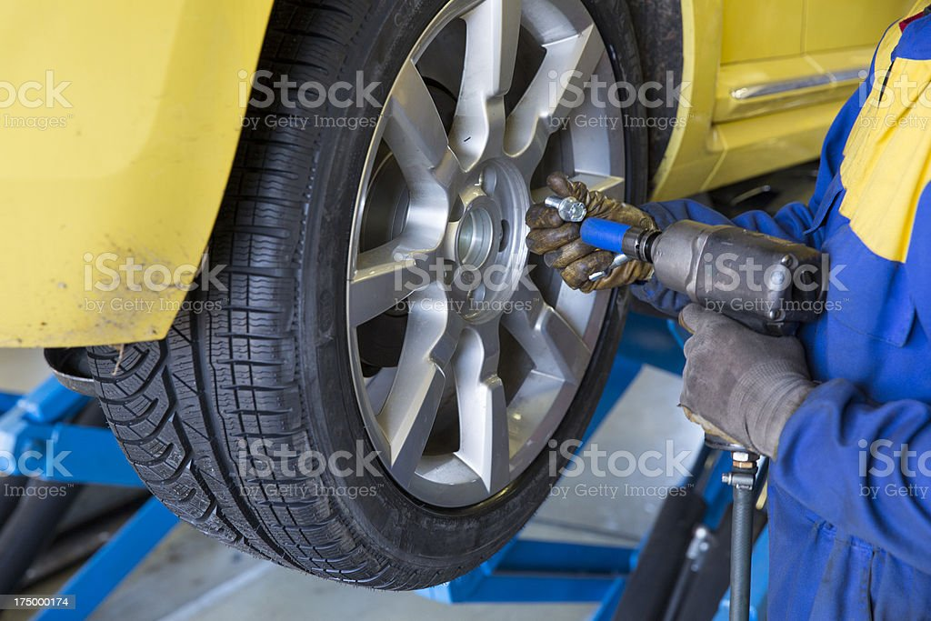 In auto repair shop...Auto mechanic is changin tire royalty-free stock photo