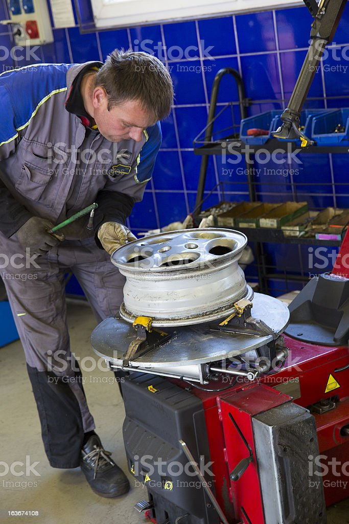 In auto repair shop...Auto mechanic is fixing alloy wheel royalty-free stock photo