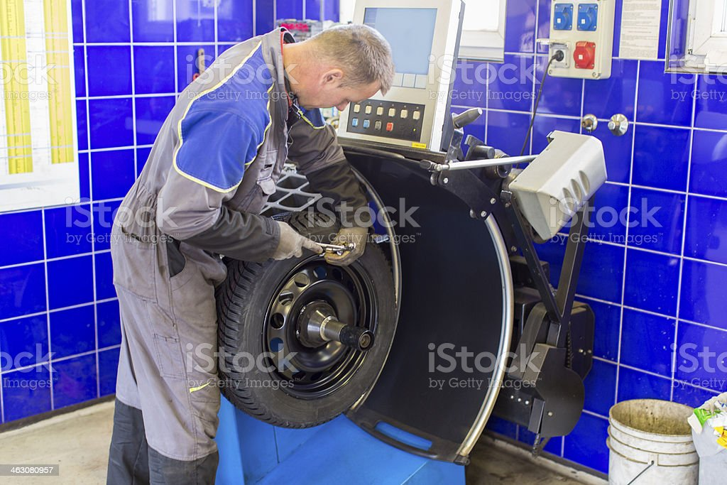 In auto repair shop...Car mechanic is  balancing winter tire royalty-free stock photo