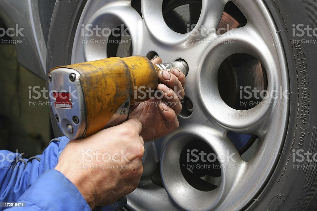 In auto repair shop...Car mechanic is changing tire royalty-free stock photo