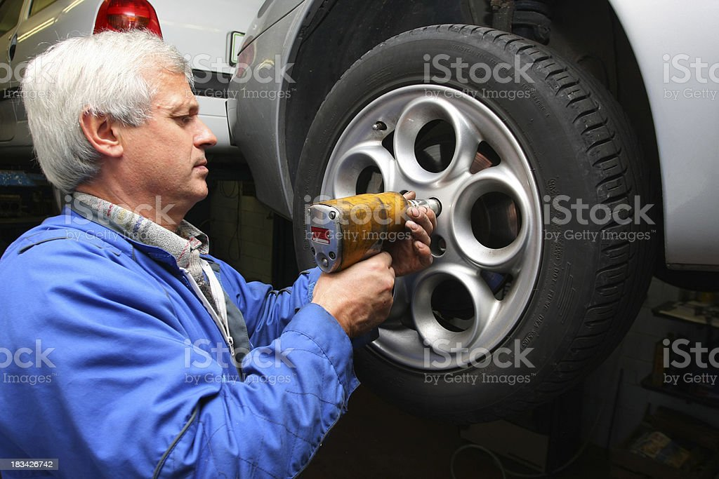 In auto repair shop...Car mechanic is changing tire stock photo