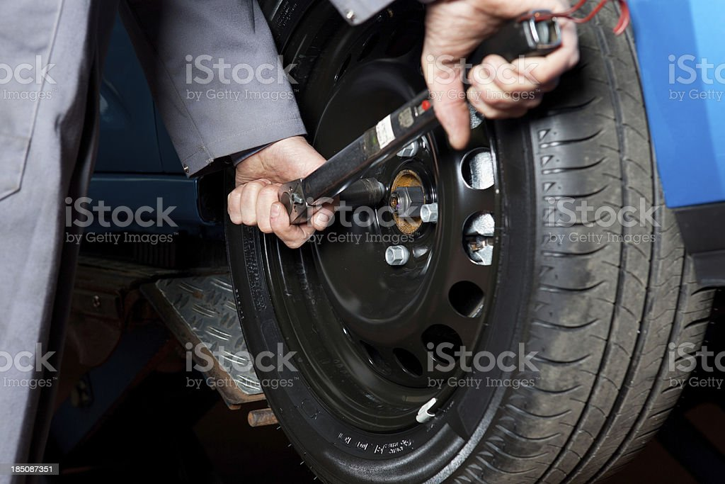 In auto repair shop....Car mechanic is changing tire stock photo