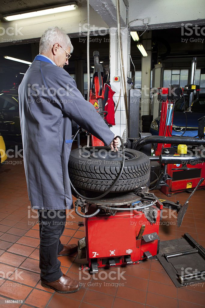 In auto repair shop...Car mechanic is checking tire air pressure stock photo