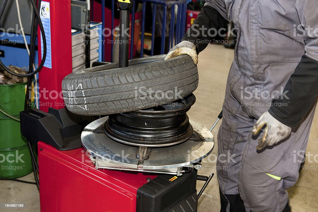 In auto repair shop...Car mechanics is  balancing winter tire stock photo