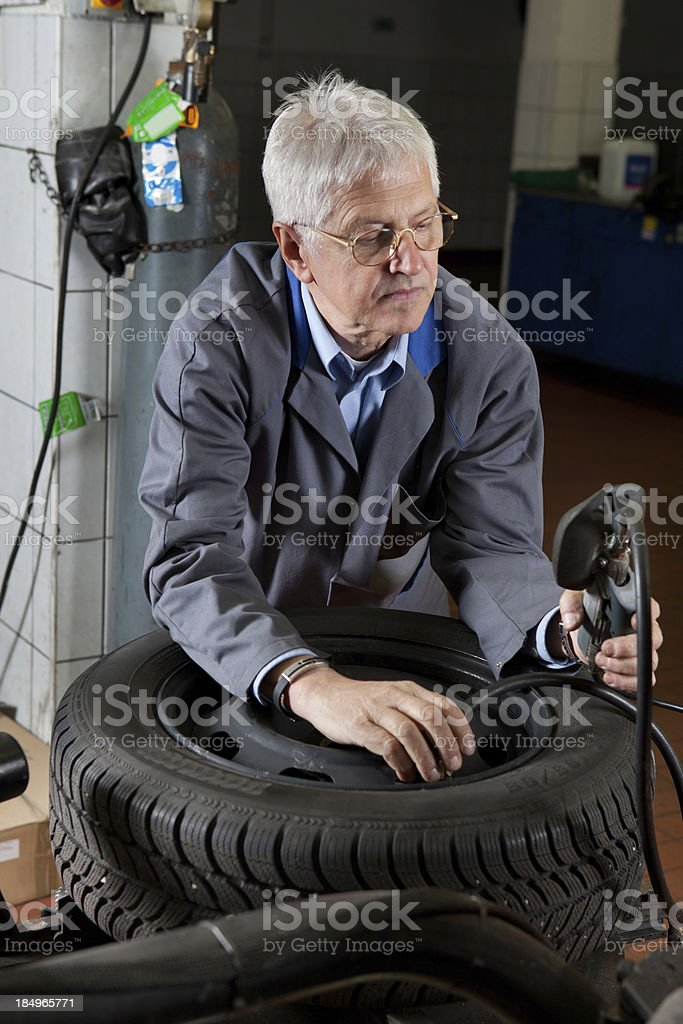 In auto repair shop...Ccar mechanic is checking tire air pressure stock photo