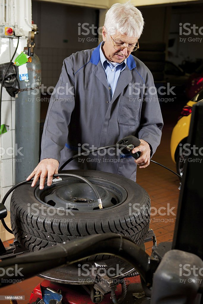 In auto repair shop...Ccar mechanic is checking tire air pressure royalty-free stock photo