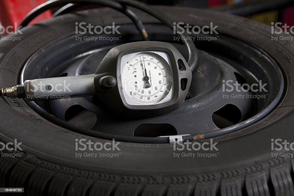 In auto repair shop...Tire with pressure gauge stock photo