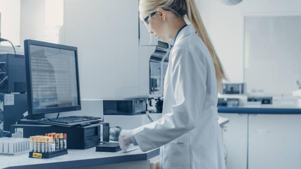 In der Bio Technological Laboatory Female Research Scientist analysiert Test Tube in Medical Machine, Works with Blood, Genetische Materialproben. – Foto